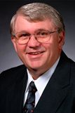 Man with gray hair and glasses in a suit.